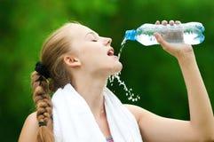 Acqua potabile della donna dopo l'esercitazione Fotografia Stock Libera da Diritti