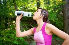 Acqua potabile della donna dopo un allenamento all'aperto Fotografia Stock Libera da Diritti