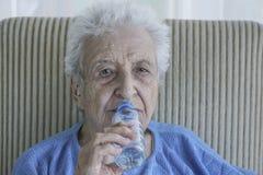 Acqua potabile della donna maggiore Immagine Stock