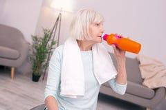 Acqua potabile della donna senior piacevole dopo un allenamento Fotografia Stock Libera da Diritti