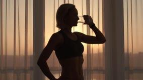Acqua potabile della donna sportiva a casa sulla mattina soleggiata archivi video