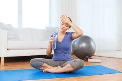 Acqua potabile della donna stanca dopo l'allenamento a casa Immagine Stock Libera da Diritti
