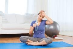 Acqua potabile della donna stanca dopo l'allenamento a casa Immagini Stock Libere da Diritti