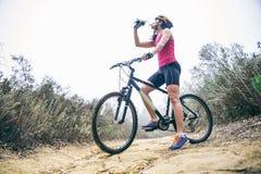 Acqua potabile della donna su una bicicletta Fotografia Stock