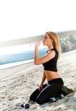 Acqua potabile della donna sulla spiaggia Fotografia Stock Libera da Diritti