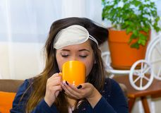 Acqua potabile della donna ubriaca in una tazza arancio, dopo un partito, concetto di postumi di una sbornia fotografia stock