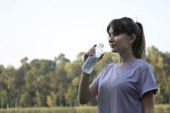 Acqua potabile della giovane bella donna in parco fotografia stock libera da diritti
