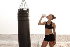 Acqua potabile della giovane bella ragazza allegra del pugile alla spiaggia Immagine Stock