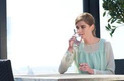 Acqua potabile della giovane donna ad un restaura di aria aperta Immagini Stock Libere da Diritti