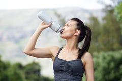 Acqua potabile della giovane donna adatta dopo l'allenamento Fotografie Stock