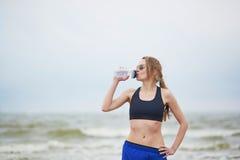 Acqua potabile della giovane donna corrente di forma fisica sulla spiaggia Fotografia Stock Libera da Diritti