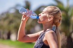 Acqua potabile della giovane ragazza bionda durante pareggiare di mattina fotografia stock libera da diritti