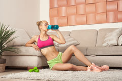 Acqua potabile della ragazza adulta sportiva dopo l'allenamento domestico Fotografia Stock Libera da Diritti