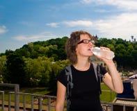 Acqua potabile della ragazza all'aperto Fotografia Stock