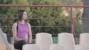Acqua potabile della ragazza bella di forma fisica da una bottiglia dopo la formazione allo stadio archivi video