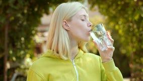 Acqua potabile della ragazza di bellezza da vetro sul parco verde Concet pulito dell'acqua di salute video d archivio