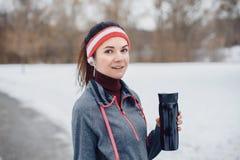 Acqua potabile della ragazza dopo avere corso all'aperto fotografia stock libera da diritti