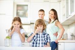 Acqua potabile della ragazza e del ragazzo con calce Fotografia Stock