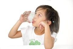 Acqua potabile della ragazza sveglia su fondo bianco Fotografia Stock