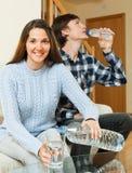 Acqua potabile delle coppie dalle bottiglie Fotografie Stock Libere da Diritti