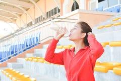 Acqua potabile delle giovani donne dopo l'esercizio Immagine Stock