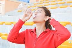Acqua potabile delle giovani donne dopo l'esercizio Fotografie Stock Libere da Diritti