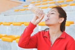 Acqua potabile delle giovani donne dopo l'esercizio Immagine Stock Libera da Diritti