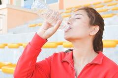 Acqua potabile delle giovani donne dopo l'esercizio Fotografia Stock Libera da Diritti