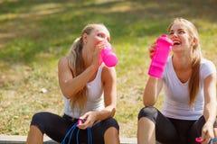 Acqua potabile delle ragazze felici dopo un allenamento su uno sfondo naturale Concetto sano di stile di vita Immagini Stock