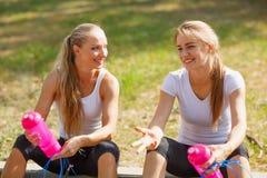 Acqua potabile delle ragazze felici dopo un allenamento su uno sfondo naturale Concetto sano di stile di vita Immagine Stock