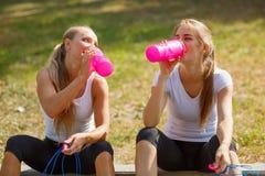 Acqua potabile delle ragazze felici dopo un allenamento su uno sfondo naturale Concetto sano di stile di vita Immagine Stock Libera da Diritti