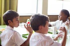 Acqua potabile dello scolaro dalla bottiglia fotografie stock