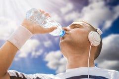 Acqua potabile dello sportivo dalla bottiglia di plastica dopo la formazione Fotografia Stock
