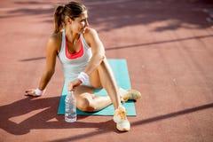 Acqua potabile di rilassamento e della giovane donna sportiva dopo la formazione fotografie stock