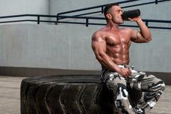 Acqua potabile di riposo e dell'uomo in buona salute dopo l'esercitazione nella palestra Fotografia Stock