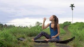 Acqua potabile e sorridere della donna, sedentesi sulla stuoia sul fondo tropicale del natute video d archivio