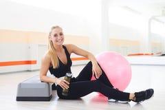 Acqua potabile felice e sorridente della donna dopo l'allenamento di aerobica Immagini Stock Libere da Diritti