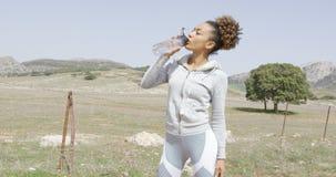 Acqua potabile femminile sull'allenamento Immagine Stock