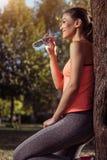 Acqua potabile sorridente della ragazza in abiti sportivi dopo la formazione Immagini Stock