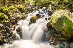 Acqua precipitante a cascata fra le rocce Fotografia Stock