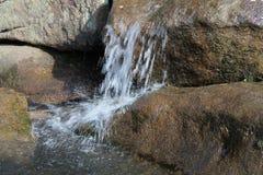 Acqua precipitante sulle rocce Fotografie Stock Libere da Diritti