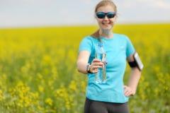 Acqua pulita nella bottiglia e nella donna prima dell'allenamento Forma fisica e Fotografie Stock Libere da Diritti