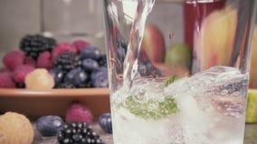 Acqua pura del movimento lento con ghiaccio sui precedenti delle bacche stock footage