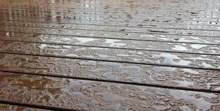 Acqua in rilievo con le riflessioni sulla piattaforma di legno di Brown scuro Immagini Stock Libere da Diritti
