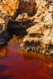 Acqua rossa e costa di pietra vulcanica nel Cipro immagini stock libere da diritti