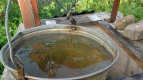 Acqua sporca dal pozzo Ecologia del pianeta La donna cade la catena con il secchio nel pozzo rustico per estrarre l'acqua archivi video