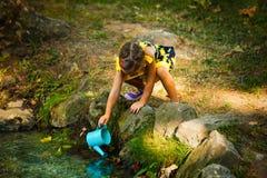 Acqua sveglia di tiraggio della bambina in secchio dalla corrente fotografia stock libera da diritti
