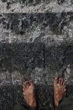 Acqua in una fontana e nei piedi umani fotografia stock