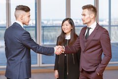Acquaintance with a new co-worker. Acquaintance. Handsome businessmen getting acquainted in the office with new partners stock image