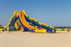 Acquascivolo gonfiabile sulla spiaggia del mare di Azov Immagine Stock Libera da Diritti
